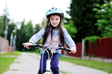 Adorable kid girl in blue helmet riding her bike