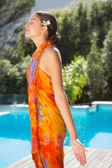 Brunette in sarong standing with arms out by the pool