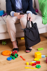 Working lady sitting on couch surrounded by clothes and toys