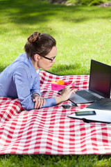 Working lady typing on her laptop in the park