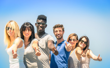 Group of multiracial happy friends with thumbs up