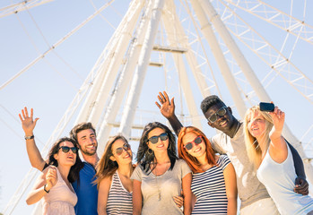 Group of multiracial friends taking a selfie at ferris wheel
