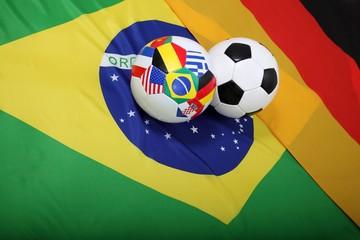 Fussbälle mit Flaggen auf Flagge von Brasilien und Deutschland