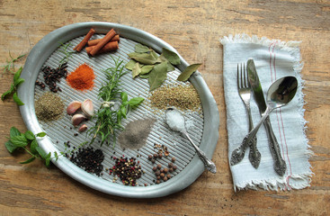 Herbs and spices on a metal tray with cutlery