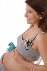 Schwangere Frau mit Babyschuh auf dem Bauch