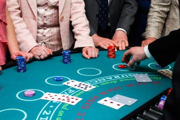 People placing bets on Black Jack card game