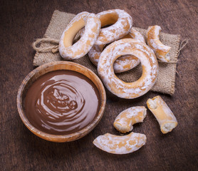 chocolate cream and bagels on dark wood background