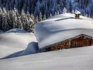 verschneite Schihütte am Waldrand in HDR