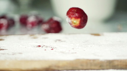 Strawberries falling on kitchen board, super slow motion