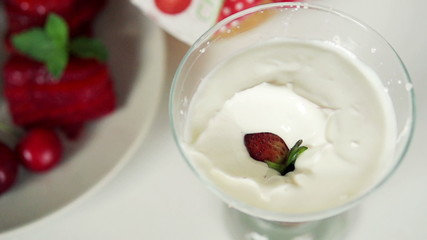Strawberries falling into yoghurt dessert, super slow motion