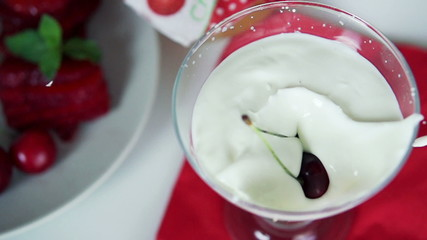 Cherry falling in yoghurt dessert, super slow motion
