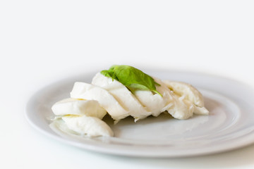 Slices of italian mozzarella with leaves of basil
