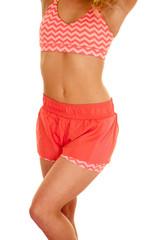 blond woman orange shorts sports bra body