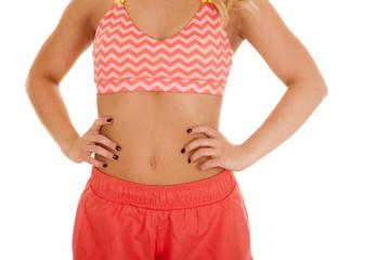 blond woman orange shorts sports bra close hands stomach
