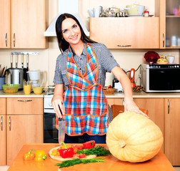 Woman at the kitchen with a big pumpkin