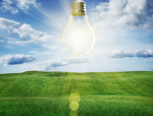 Light bulb with a sunshine inside in field. Environment, eco tec