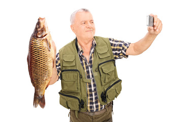 Mature fisherman holding a fish and taking selfie