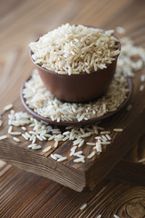 Raw brown rice over rustic wooden background, close-up