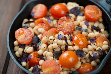 Close-up of roasted white beans and red tomatoes in a frying pan