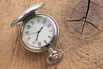 Silver pocket watch on wooden background