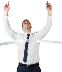 Smiling businessman crossing finishing line