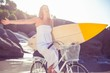 Beautiful surfer in sundress on bike holding surfboard at the be
