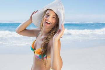 Beautiful girl on the beach laughing in white straw hat and biki