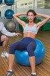 Trainer helping his client doing sit up on exercise ball