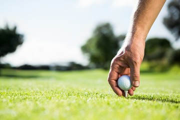 Golfer placing golf ball on tee