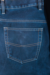 fragment of back pocket blue jeans, background