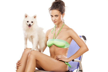 pretty girl posing on a beach chair with a small dog on her knee