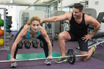 Personal trainer coaching female bodybuilder lifting barbell