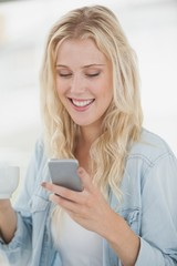 Cute blonde texting on phone