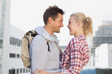 Hip young couple smiling at each other
