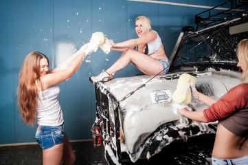 Sexy playful women washing car with fun