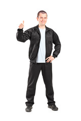 Young man in black tracksuit giving a thumb up