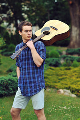 Young stylish hipster man with guitar in the park