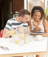 Young attractive mixed race couple working with tablet