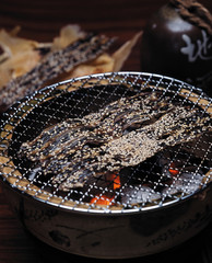 Slices of dried fish on grill