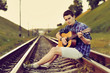 Handsome man with guitar on railway road