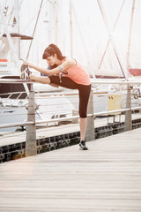 Young beautiful girl stretching against railing before exercise