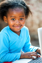 Cute african girl typing on laptop.