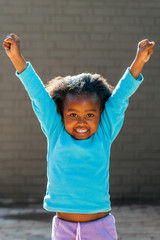 Happy african girl raising arms high.