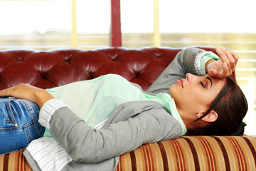 Tired woman sleeping on the coach at office