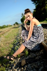 Female model sits on railroad