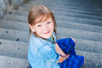Portrait of a cute little girl sitting on steps outdoors
