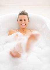 Happy young woman playing with foam in bathtub