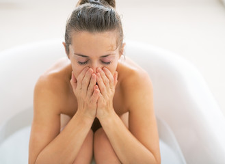 Stressed young woman sitting in bathtub