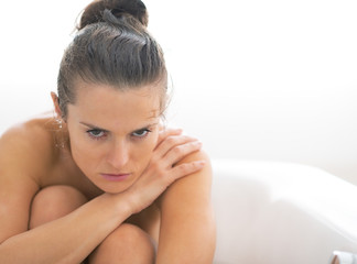Frustrated young woman sitting in bathtub