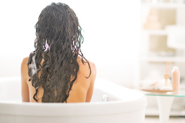 Young woman sitting in bathtub. rear view